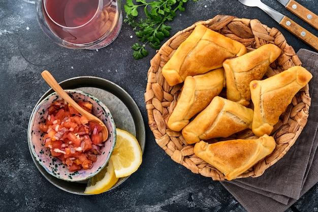 Empanadas fritas com coentro, carne, ovo, tomate e molho de pimenta em fundo preto. prato típico chileno. conceito de dia da independência da américa latina e do chile.