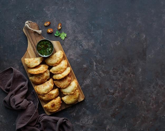 Empanadas fritas com molho. vista do topo.