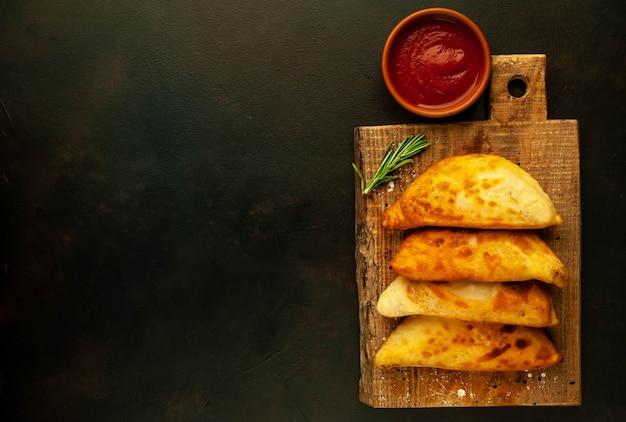Empanadas fritas da américa latina com molho de tomate e espaço para seu texto de cópia