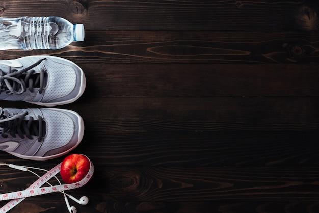 Emparelhe calçados esportivos, fones de ouvido, maçã e garrafa de água em madeira preta