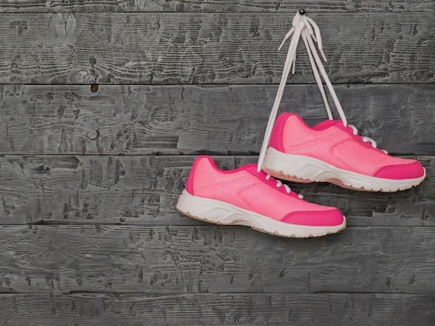 Emparelhe os tênis femininos rosa pendurados pelos cadarços na parede de madeira.