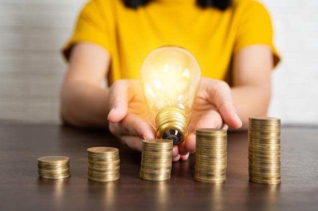Empilhadas de moedas de dinheiro com show de mulher e segurando a lâmpada