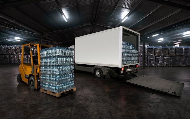 Empilhadeira amarela carregando o caminhão com água engarrafada dentro do armazém