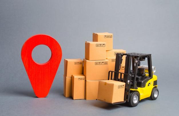 Empilhadeira amarela com caixas de papelão e um pino de posição vermelho. localizando pacotes e mercadorias