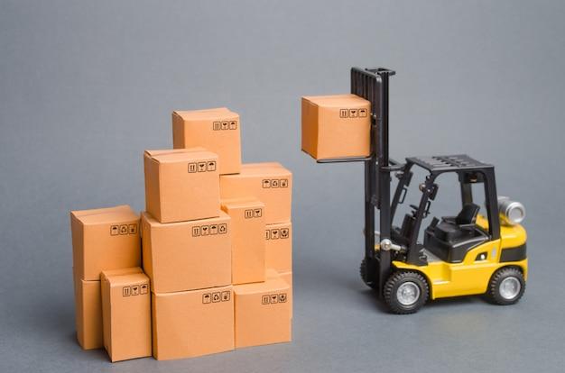 Empilhadeira amarela levanta uma caixa de papelão para o topo de uma pilha de pilha de caixas. estoque de armazém