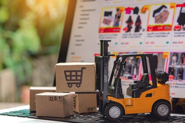 Empilhadeira carregadeira palete com caixas de papel ou pacote no laptop, logística e serviço de entrega para compras online