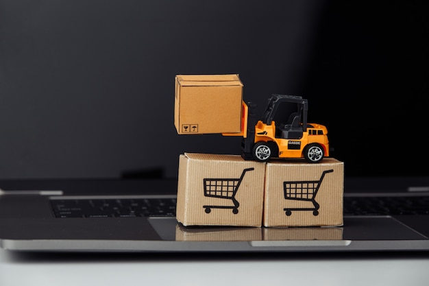 Empilhadeira de brinquedo com caixas de papelão no teclado. logística e conceito de atacado.