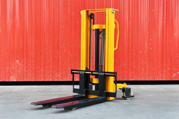 Empilhadeira elétrica amarela na frente do armazém