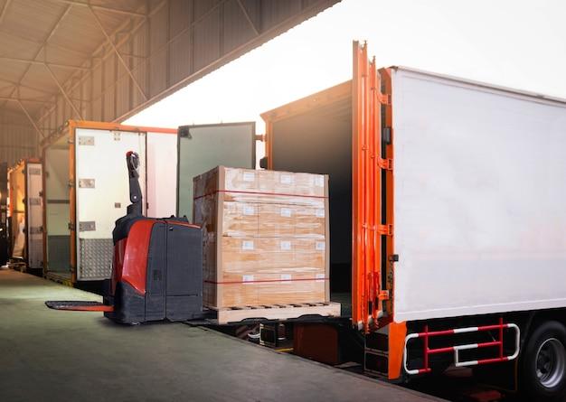 Empilhadeira elétrica carregando caixas de pacotes em caminhões de contêineres estacionados no armazém da doca