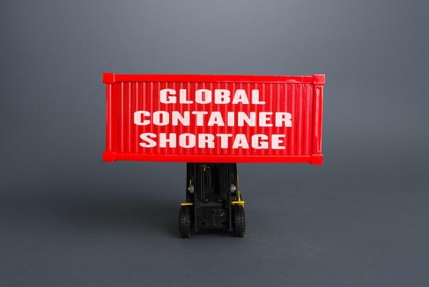 Empilhadeira levanta o contêiner com a inscrição escassez de contêiner global problemas de logística