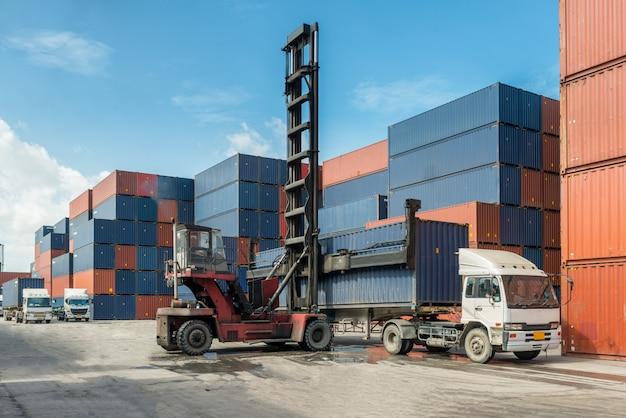 Empilhadeira que segura a carga da caixa do recipiente em docas com o caminhão para o conceito logístico da exportação da importação.