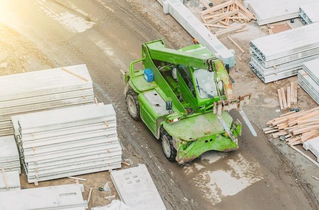 Empilhadeira verde na vista superior do canteiro de obras.