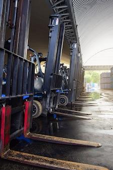 Empilhadeiras estacionadas em um armazém.
