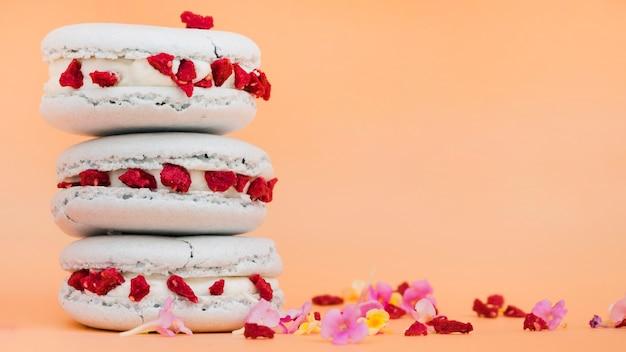 Empilhados de biscoitos com flores sobre fundo bege