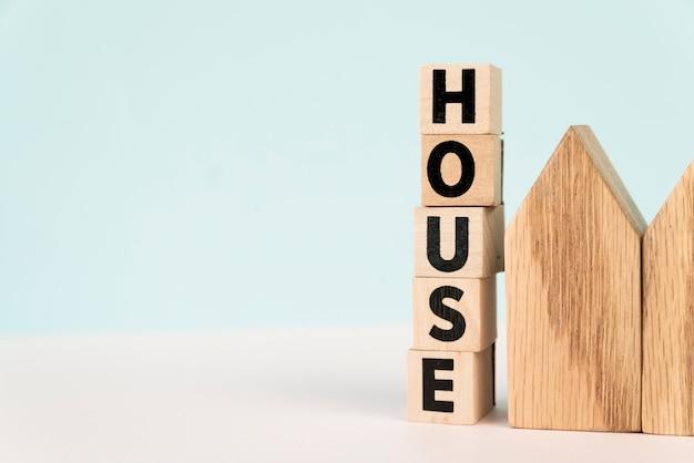 Empilhados de blocos de casa de carta perto do modelo de casa contra o fundo azul