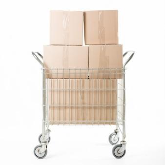 Empilhados de caixa de papelão no carrinho contra fundo branco