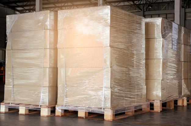 Empilhados de caixas de carga envolvendo plástico em prateleiras de paletes. armazenamento em armazém. exportação de carga.