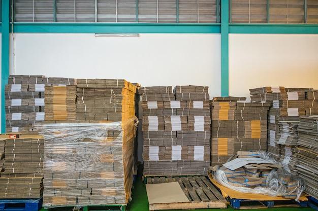 Empilhados de caixas de papelão de embalagem plana em paletes para embalagem do produto e entrega no armazém