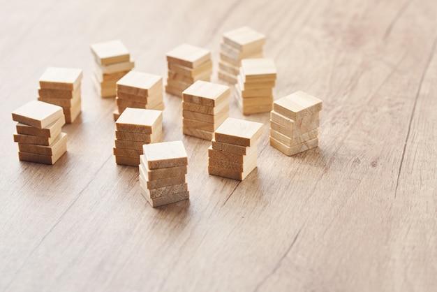 Empilhados nos blocos de madeira das torres na tabela de madeira com espaço da cópia. conceito de equipe e liderança