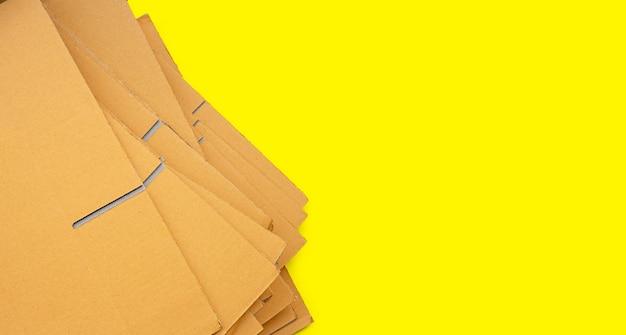 Empilhamento de caixas de papelão, papel ondulado em fundo amarelo. vista do topo