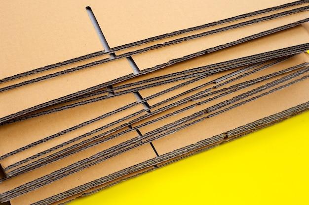 Empilhamento de caixas de papelão, papel ondulado em fundo amarelo.