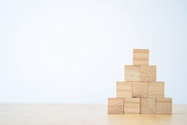 Empilhamento de cubos de madeira em branco na mesa com espaço de cópia para o texto de entrada e o ícone do infográfico.
