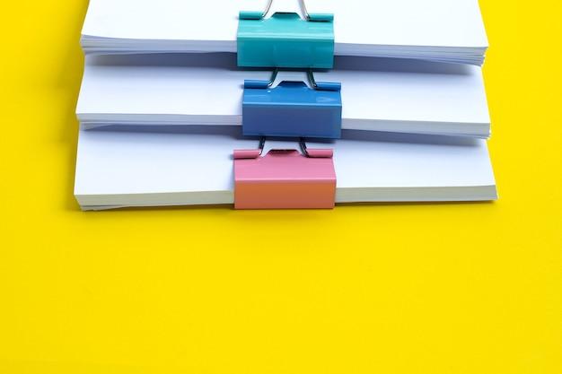 Empilhamento de documentos comerciais com clipes de pasta coloridos na superfície amarela