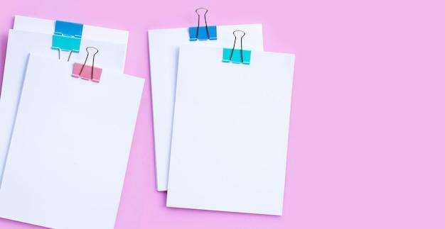 Empilhamento de documentos comerciais com clipes de pasta coloridos na superfície rosa