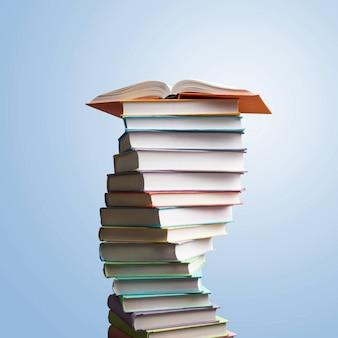 Empilhamento de livros. é um livro aberto, livros de capa dura na mesa de madeira e fundo azul. de volta à escola.