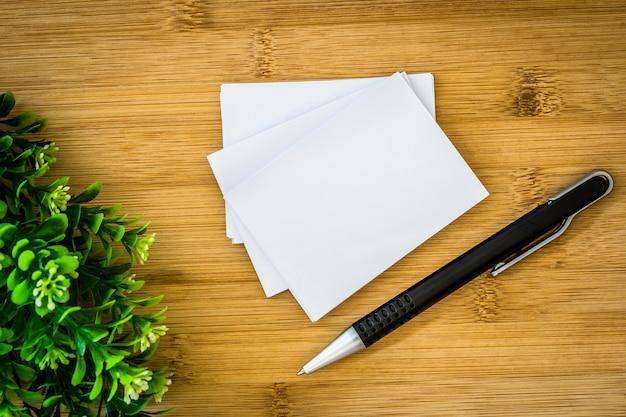 Empilhamento de maquete vazio cartão branco com caneta de elegância em fundo de madeira