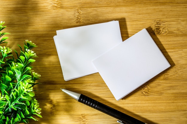 Empilhamento de maquete vazio cartão branco com caneta de elegância em um fundo de madeira