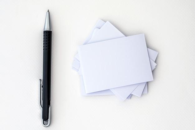 Empilhamento de maquete vazio cartão branco com caneta de elegância em um fundo de papel branco