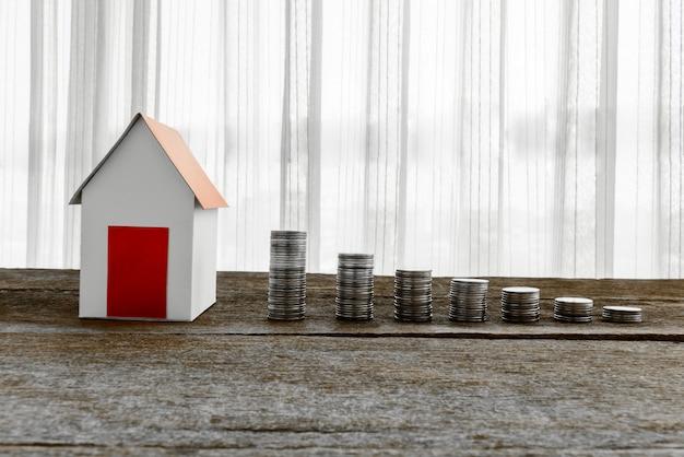 Empilhando moedas e modelo em casa para economizar com dinheiro crescente
