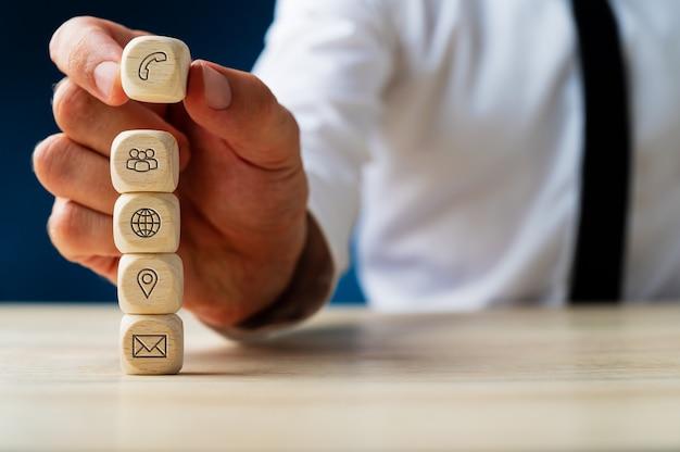 Empilhar cubos de madeira com ícones globais de informações de contato e localização