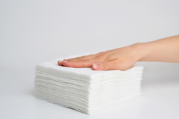 Empilhar guardanapos brancos na mão no isolamento da superfície branca