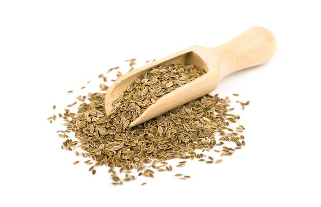 Empilhe a semente de aneto na colher, isolada no branco. fechar-se