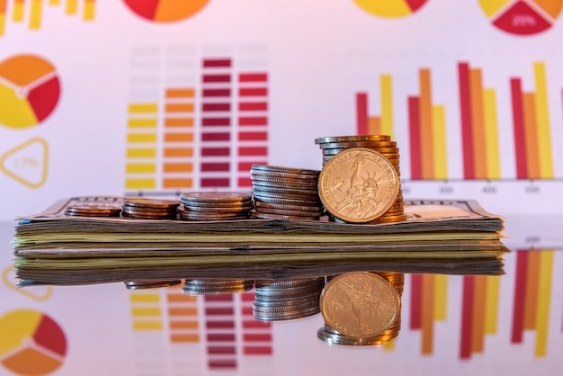 Empilhe dólares e moedas na superfície brilhante