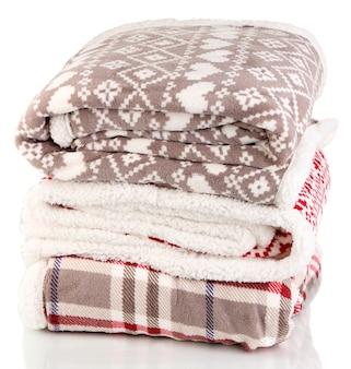 Empilhe mantas quentes isoladas na superfície branca