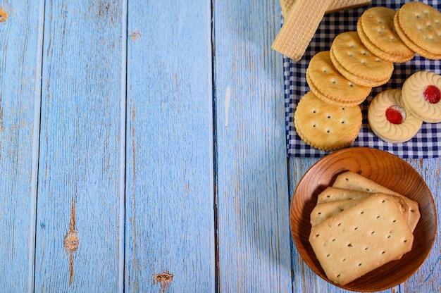 Empilhe muitos tipos de biscoitos em um prato e coloque sobre uma mesa de madeira.