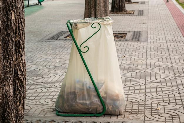 Empilhe o plástico branco do saco de lixo na beira da estrada. saco de passeio no passeio.