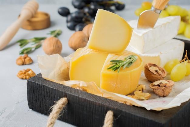 Empilhe o queijo camembert com uvas, nozes e manjericão em uma superfície de concreto cinza claro