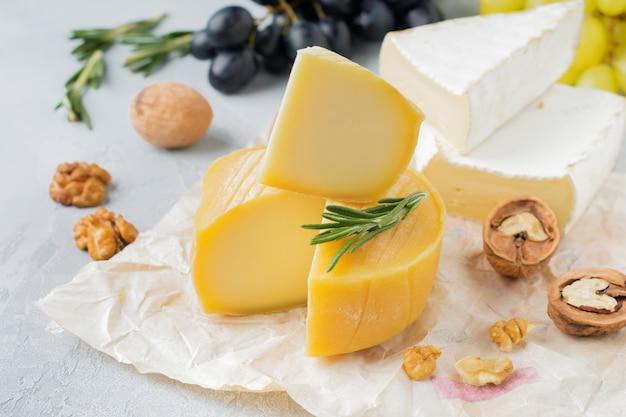 Empilhe o queijo camembert com uvas, nozes e manjericão na superfície de concreto ou pedra cinza claro. foco seletivo.