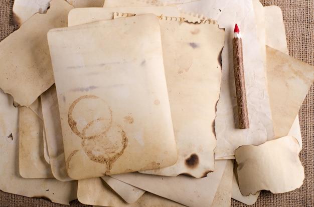 Empilhe papéis velhos, caderno e lápis de madeira na serapilheira, pano de saco.