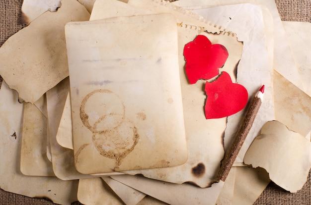 Empilhe papéis velhos, caderno, lápis de madeira e dois corações vermelhos do vintage na serapilheira, pano de saco.