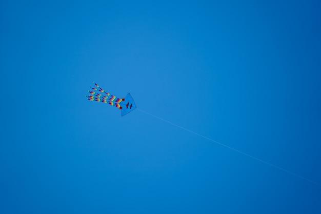 Empinando pipa em uma corda contra o céu azul, vietnã