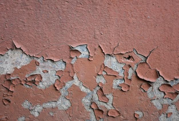 Emplastro de casca rachado no fundo da parede