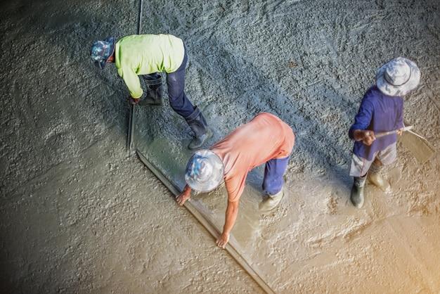 Emplastro do trabalhador no canteiro de obras, derramamento concreto durante assoalhos concreting comerciais.