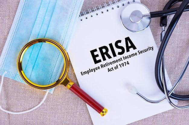 Employee retirement income security act erisa, o texto está escrito em um bloco de notas, ao lado de uma caneta, uma máscara médica descartável, um estetoscópio