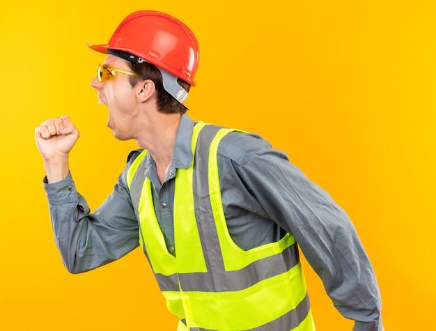 Empolgado em pé na vista de perfil, jovem construtor de uniforme usando óculos mostrando um gesto de sim