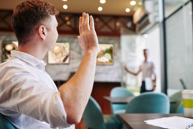 Empreendedor acenando para um colega entrando na porta do café